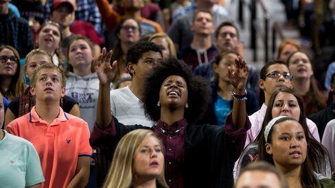 An attendee raises her hands during an opening worship song beforeSanders's speech.