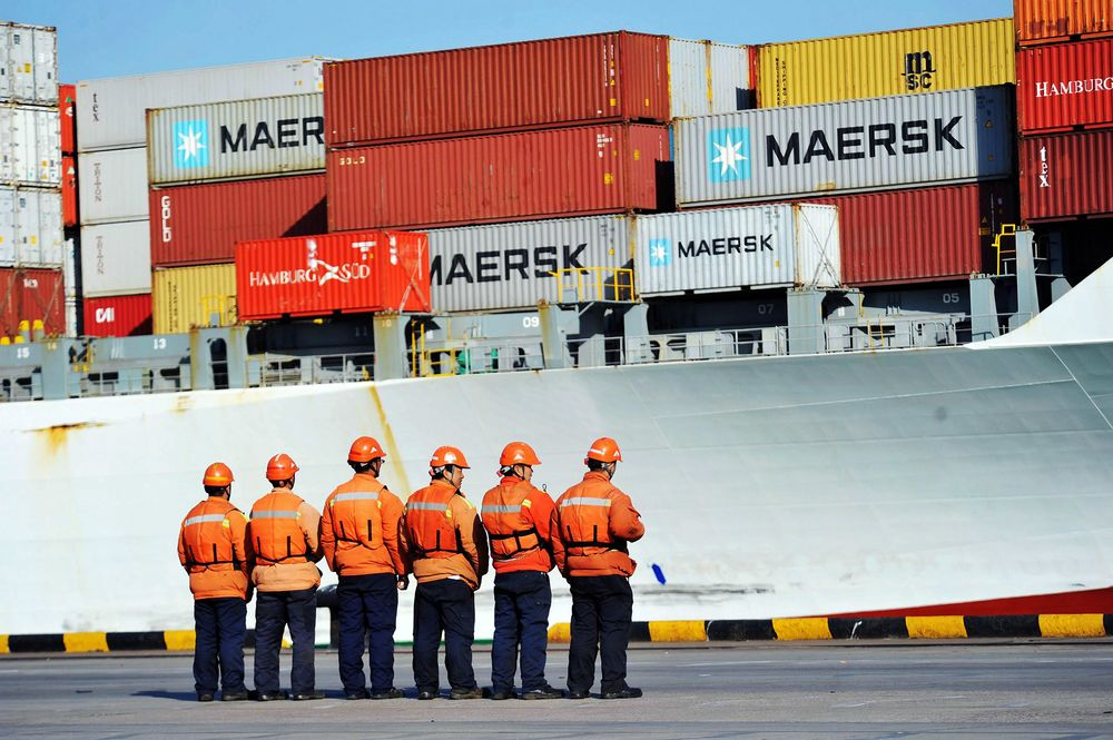 Workers stand in line next to a container ship at a port in Qingdao in China's eastern Shandong province.