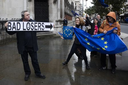 A protestor holds a sign disrupting a pro-EU demonstration outside the Royal Courts of Justice, in London.