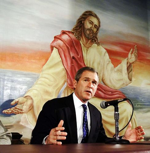 George W. Bush speaks in front of a mural of Jesus Christ while campaign in Iowa in 2000.