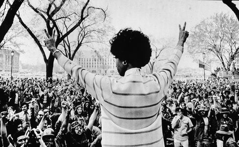 Congresswoman Shirley Chisholm gives the peace sign to a crowd of protestors as she speaks to veterans on the Washington Mall in 1971.