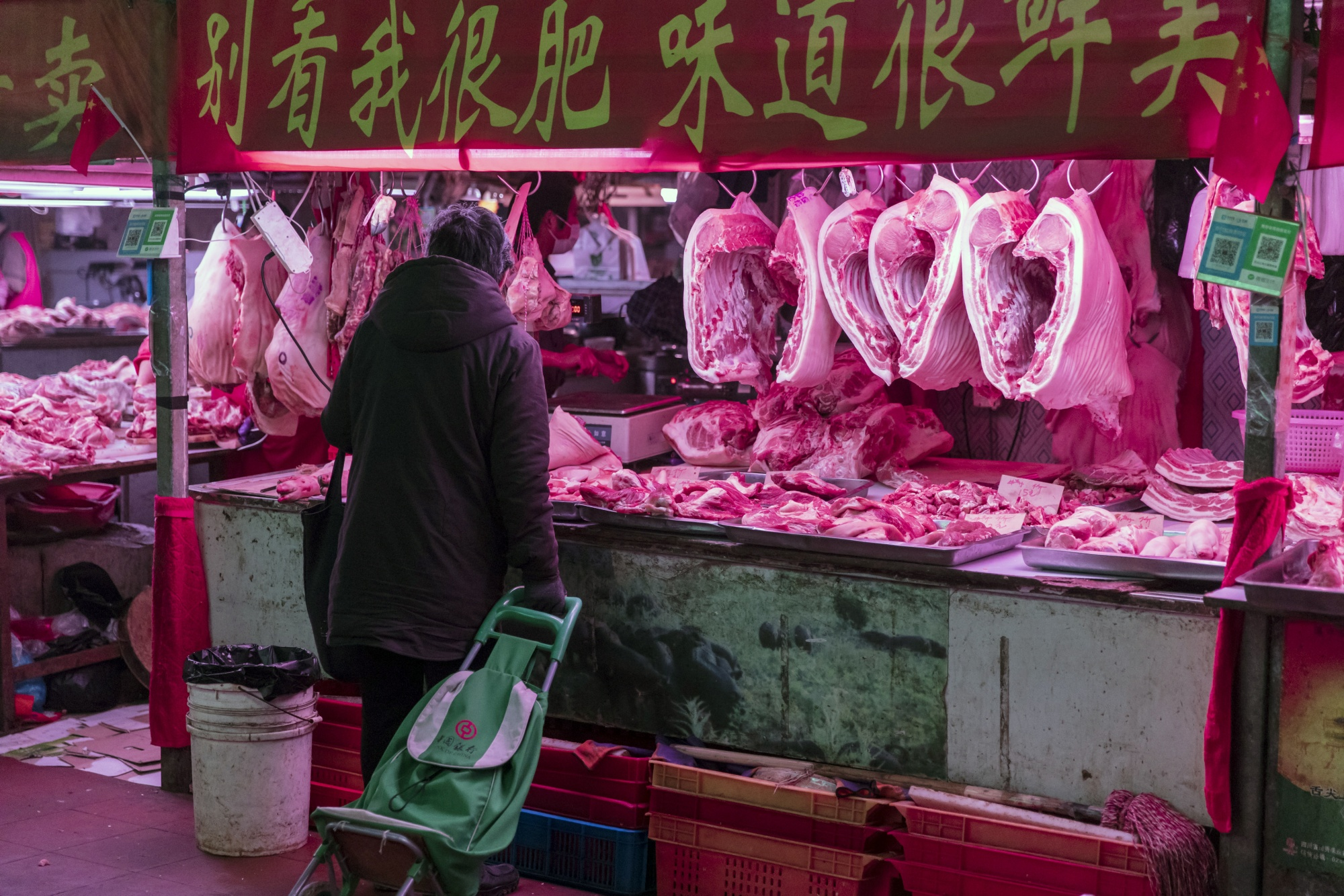 A customer buys pork at a market in Shanghai, China.