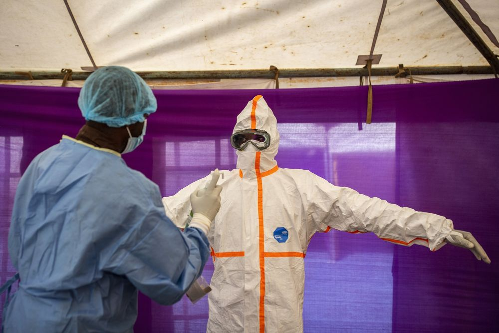 A health worker disinfects a colleague after testing patients for Covid-19 at a field hospital near Nairobi on May 4.