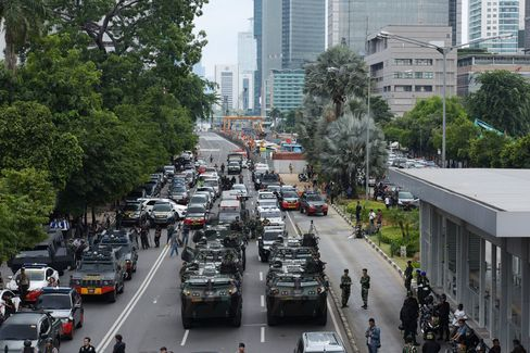 Military vehicles stand near the site of an explosion in Jakarta.