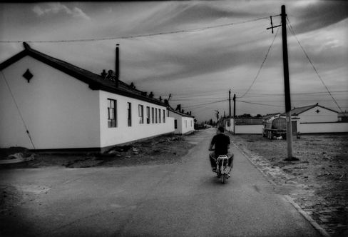 A Mongol man rides his motorbike into a government resettlement project, south of Bayanhaote.