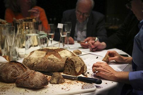 """André Soltner (background) judges one of the 15 finalists during the """"Best Baguette in NYC"""" competition."""