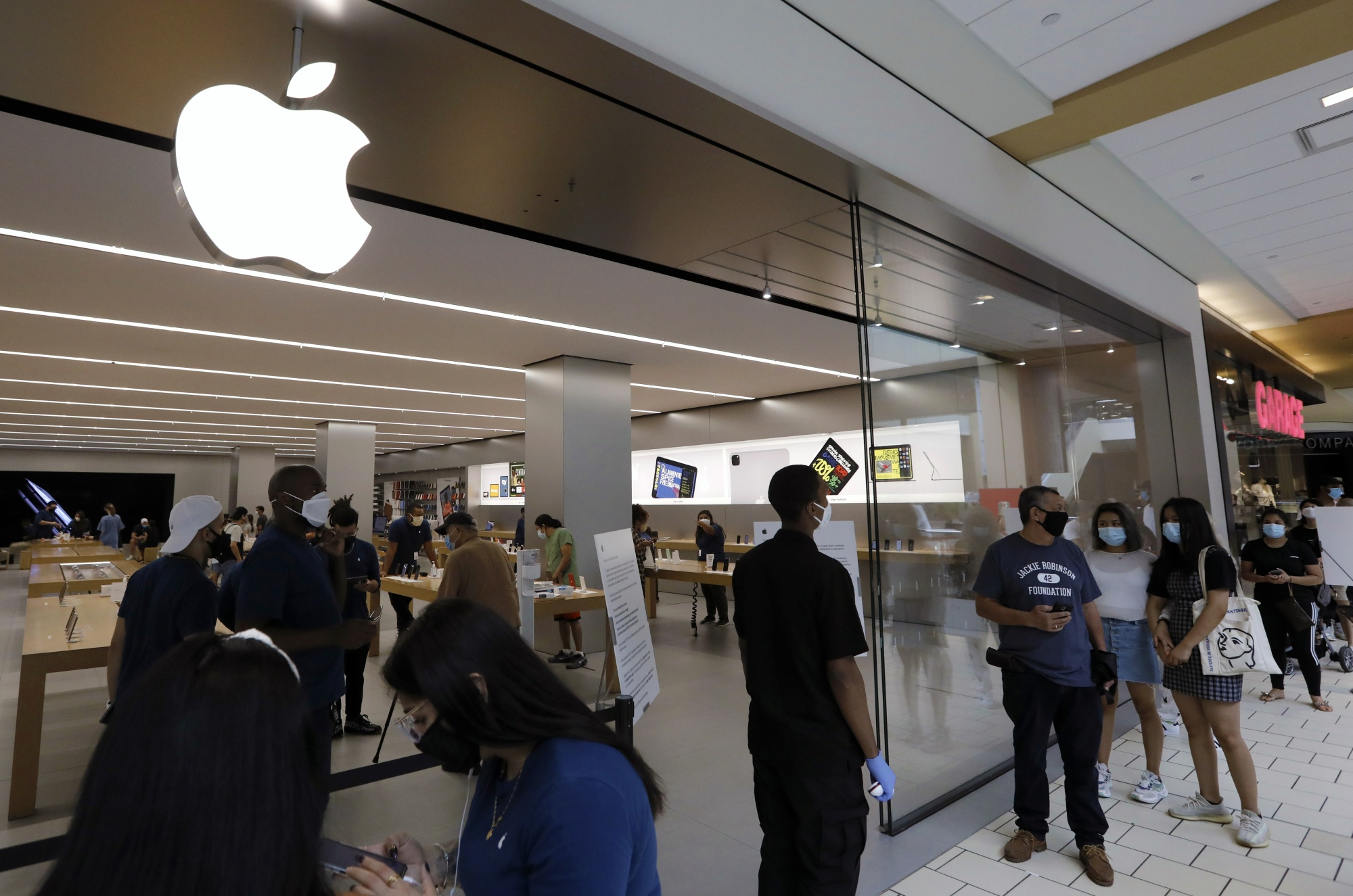 Shoppers stand in line to enter the Apple store at the Queens Center shopping mall in Queens, New York.
