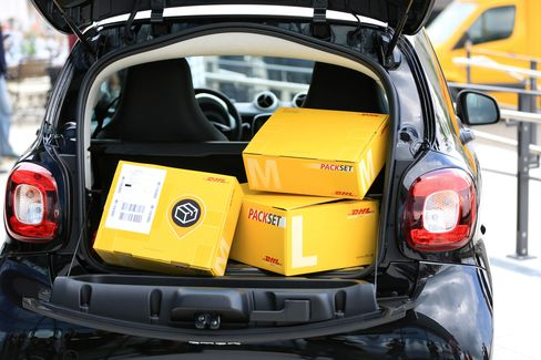DHL packages in the trunk of a Daimler Smart automobile as they unveil the service on July 25.