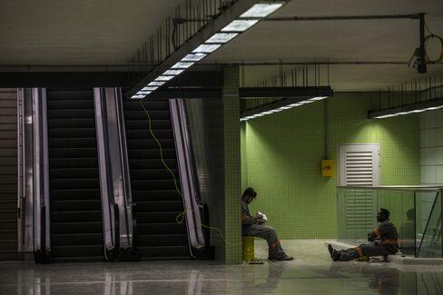 Workers sit beside escalators at the Nossa Senhora da Paz metro station in Rio de Janeiro.