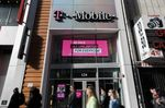 Pedestrians pass in front of a T-Mobile US Inc. store in New York, U.S.