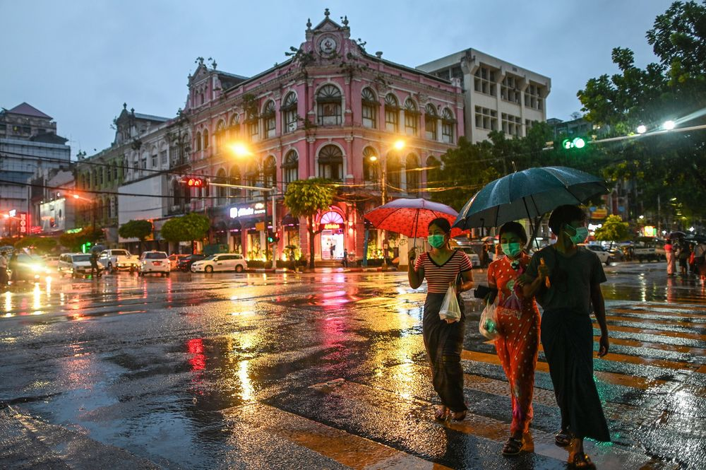 People wearing protective masks hold umbrellas as they cross a road during rainfall in Yangon, Myanmar, on June 14.