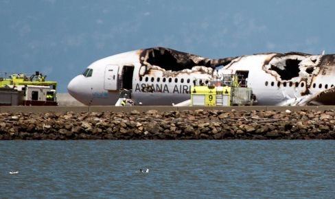A burned Asiana Airlines aircraft sits on the runway after it crashed landed at San Francisco International Airport.