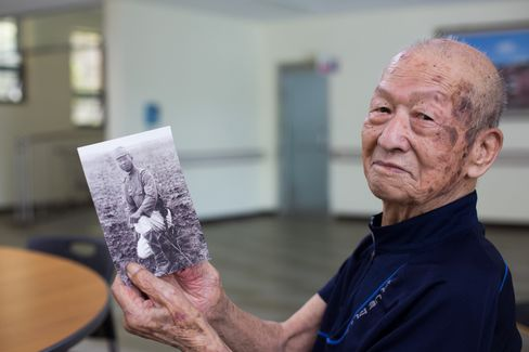 Lee Bong Moon, showing a photo of himself when he was in the Japanese army .