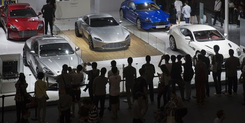 Attendees look at Aston Martin Lagonda vehicles on display during the China International Automobile Exhibition.