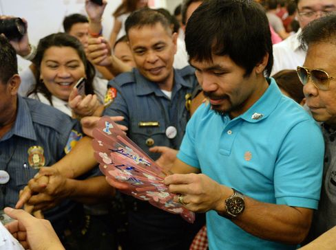 Philippine boxing icon Manny Pacquiao signs his autograph for a fan after filing his Certificate of Candidacy for senator at the Commission on Elections in Manila.