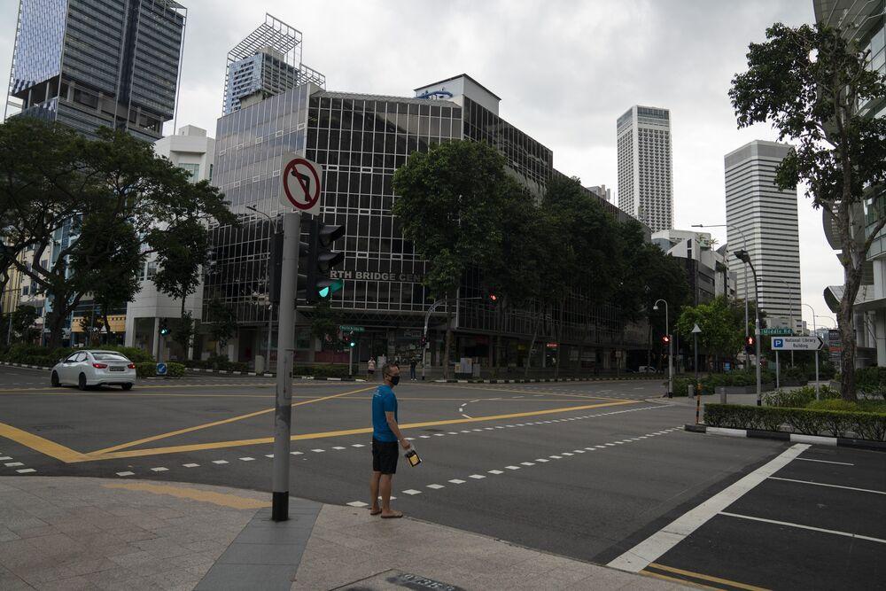 Một người đi bộ đứng tại 1 ngã ba trong thời gian phong tỏa một phần do coronavirus ở Singapore vào ngày 7 tháng 4. Ảnh: Wei Leng Tay / Bloomberg