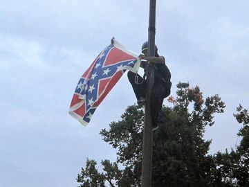 Bree Newsome of Charlotte, N.C., removes the Confederate battle flag at a monument at the statehouse in Columbia, S.C., on Saturday. She was taken into custody when she came down. The flag was raised again by capitol workers about 45 minutes later.