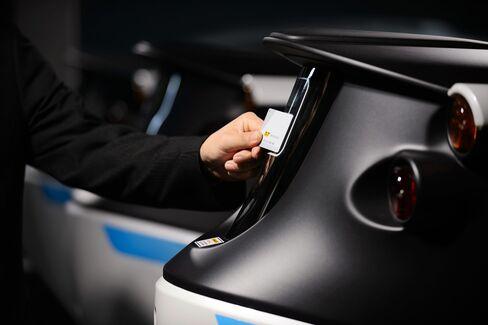 A Park24 employee unlocks a car with a key card.