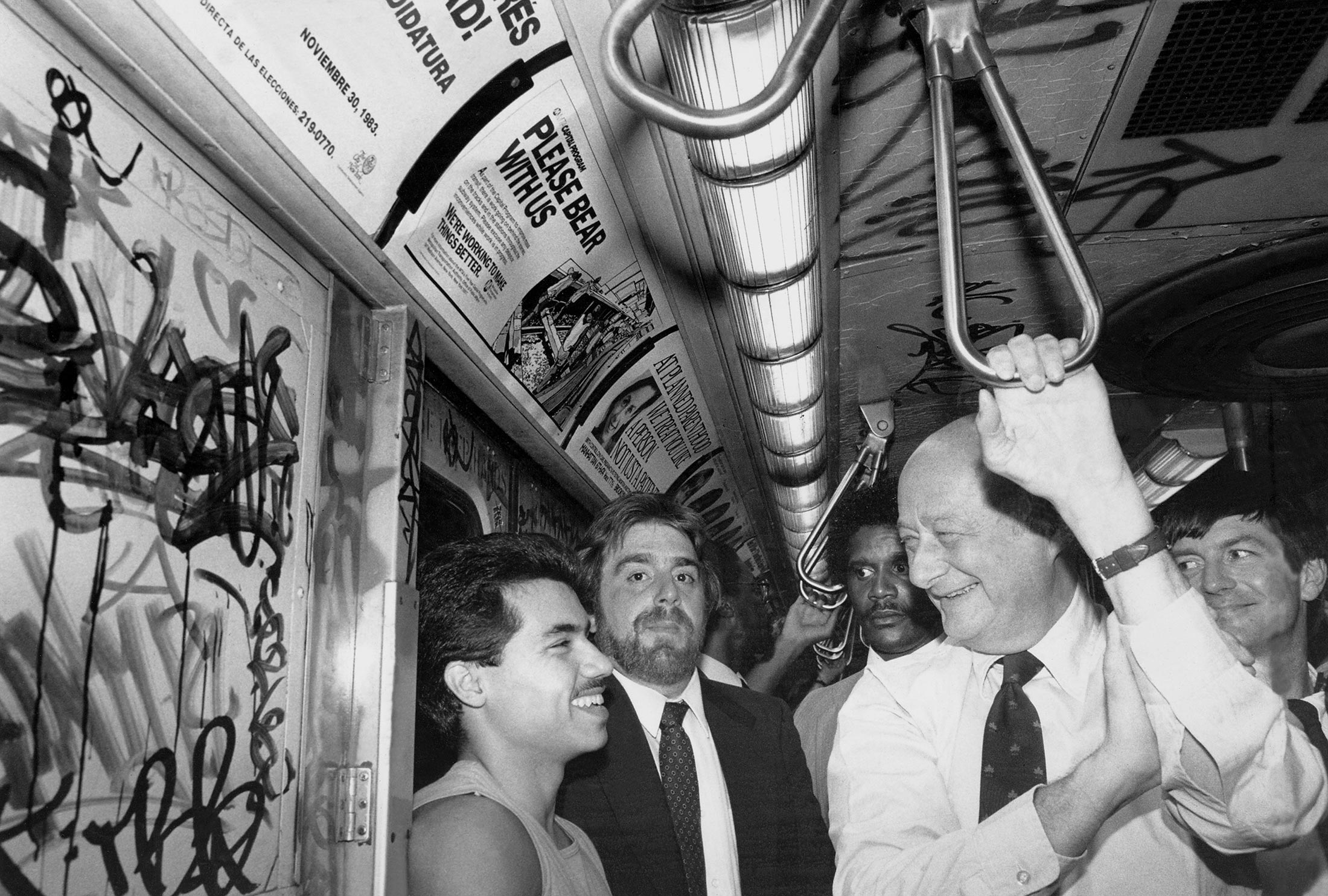 Mayor Ed Koch chats with Joey Valdez as he rides the R train