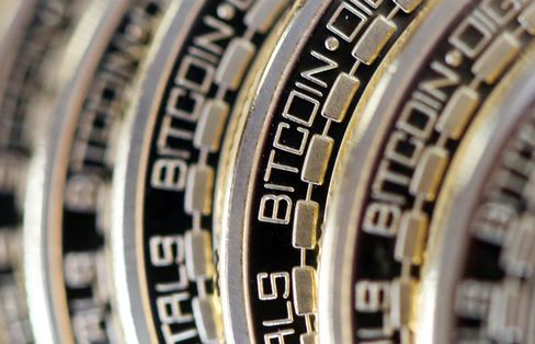 The embossed word Bitcoin sits on the edge of Bitcoins stacked in this arranged photograph in Danbury, U.K.
