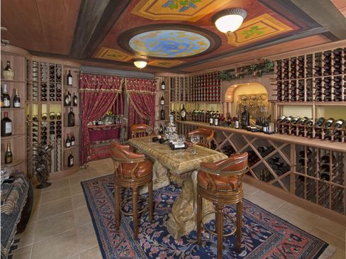 """This over-the-top """"wine grotto,"""" in a 35,700-square-foot house, is an example of combining the wine cellar and tasting room, with traditional-style wood bottle racks, artwork, fine carpet, and marble table. The house, south of Hearst Castle on California's central coast, is listed at$55 million through Sotheby's."""