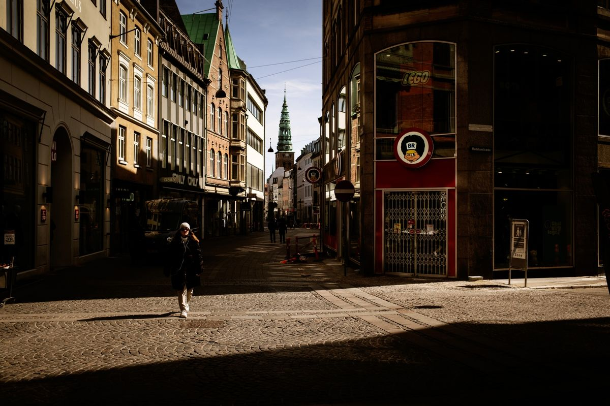 A pedestrian walks past closed stores on Storget street in Copenhagen, Denmark, on April 15.