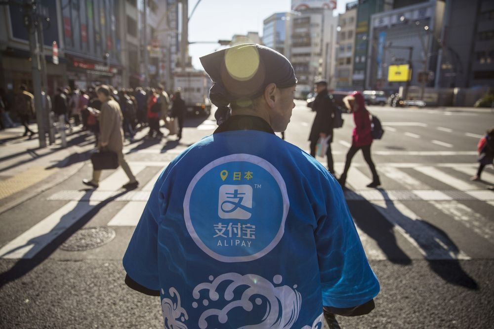 A staff member wearing a uniform featuring the logo for Ant Financial Services Group's Alipay.