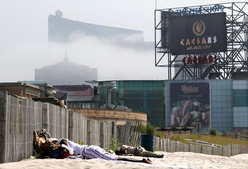 People sleep near the boardwalk in Atlantic City. The Revel can be seen looming in the background.
