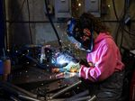 A worker welds together bumpers for three-wheeled electric vehicles at a facility in Eugene, Oregon.