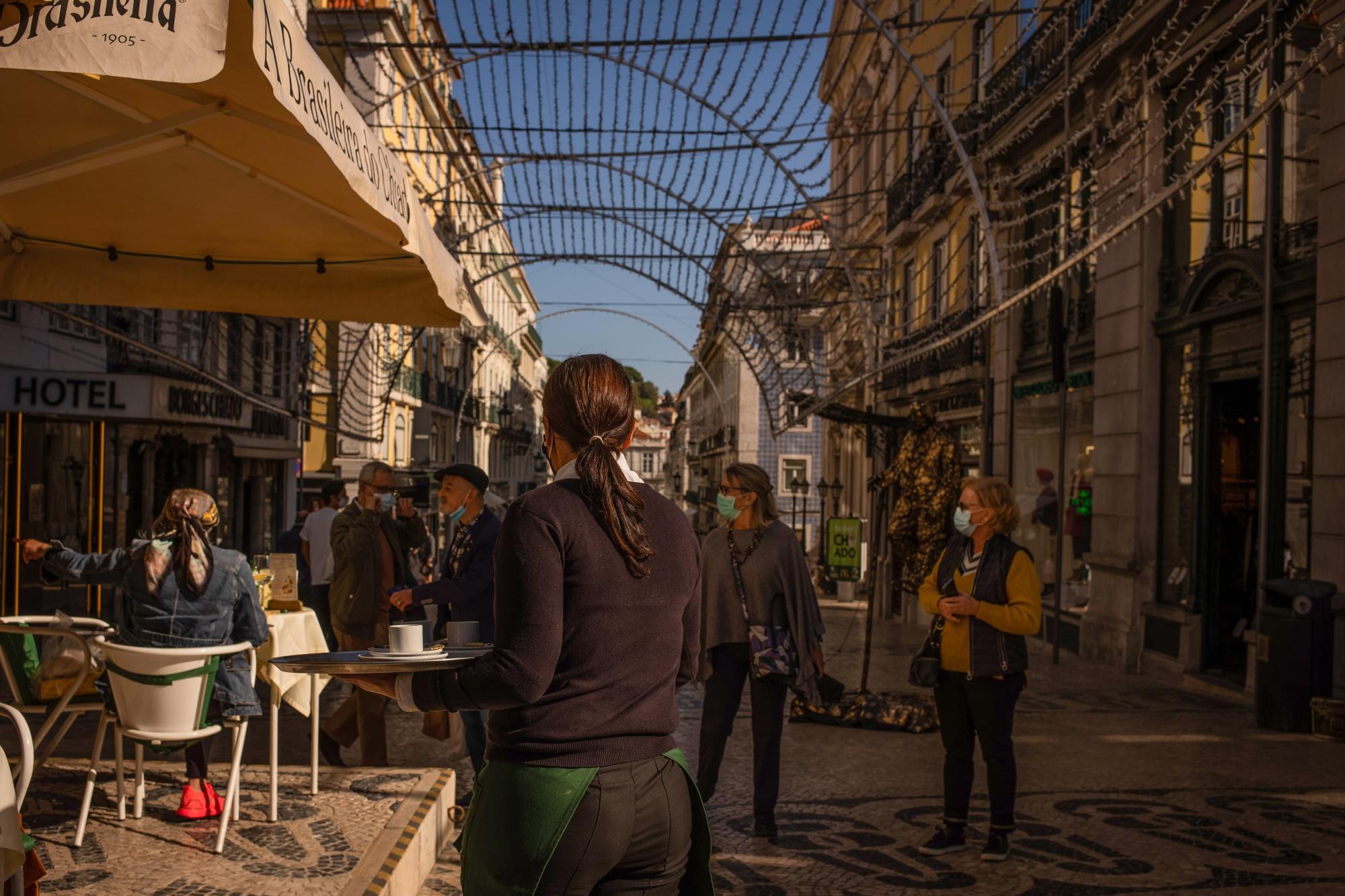 Funcionário atende clientes na esplanada de um hotel do bairro do Shiado, em Lisboa.