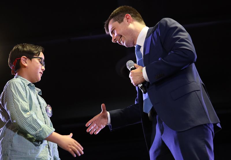 Pete Buttigieg greets Zachary on stage at a campaign event in Denver on Feb. 22.