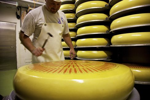 An Employee Tests a Whole Cheese for Holes