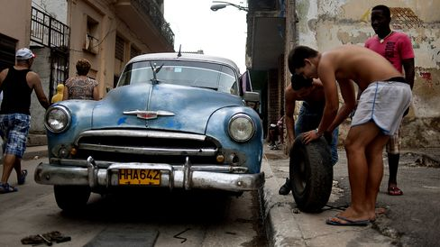 Men change the tire on an old Chevrolet.