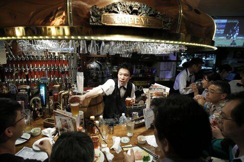 A bartender, center, serves glasses of craft beer to customers sitting at the bar of the Bakusyu Club Popeye in the Ryogoku neighborhood of Tokyo, on May 1, 2015. Photographer: Kiyoshi Ota/Bloomberg