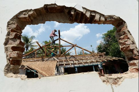 Two men dismantle the roof of a house in Jemah village on Sept 1.