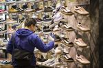 A shopper checks sneakers displayed for sale at a footwear store in the Odaiba area of Tokyo, Japan.