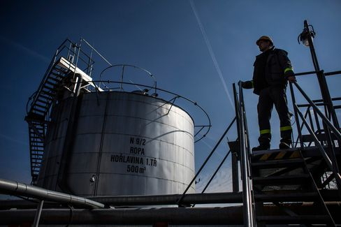 An employee stands on a platform beside an oil storage tank at an oil plant operated by MND AS in Damborice, Czech Republic, on March 23.