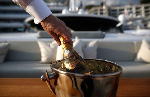 A crew member holds a magnum of Tattinger champagne during the Monaco Yacht Show.