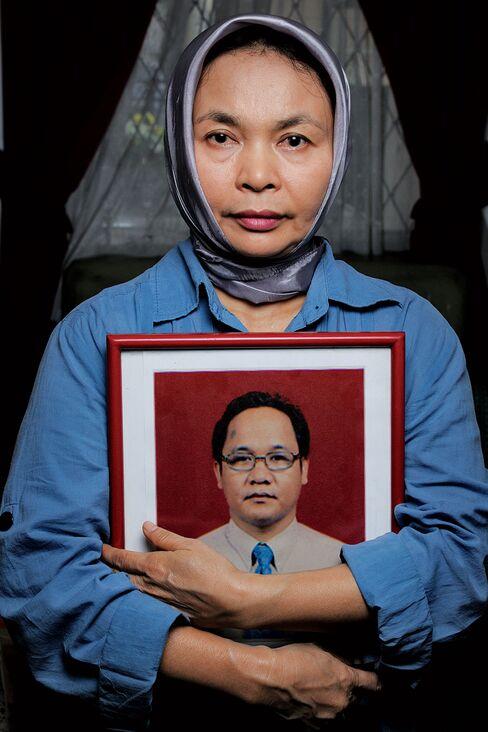 Esi Ronaldi embraces a photo of her late husband, Irzen Octa