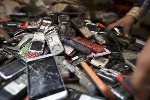 Workers sort through a pile of used mobile phones.