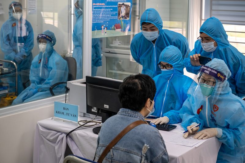 Health workers collect information from a vaccine receiver in Hanoi.