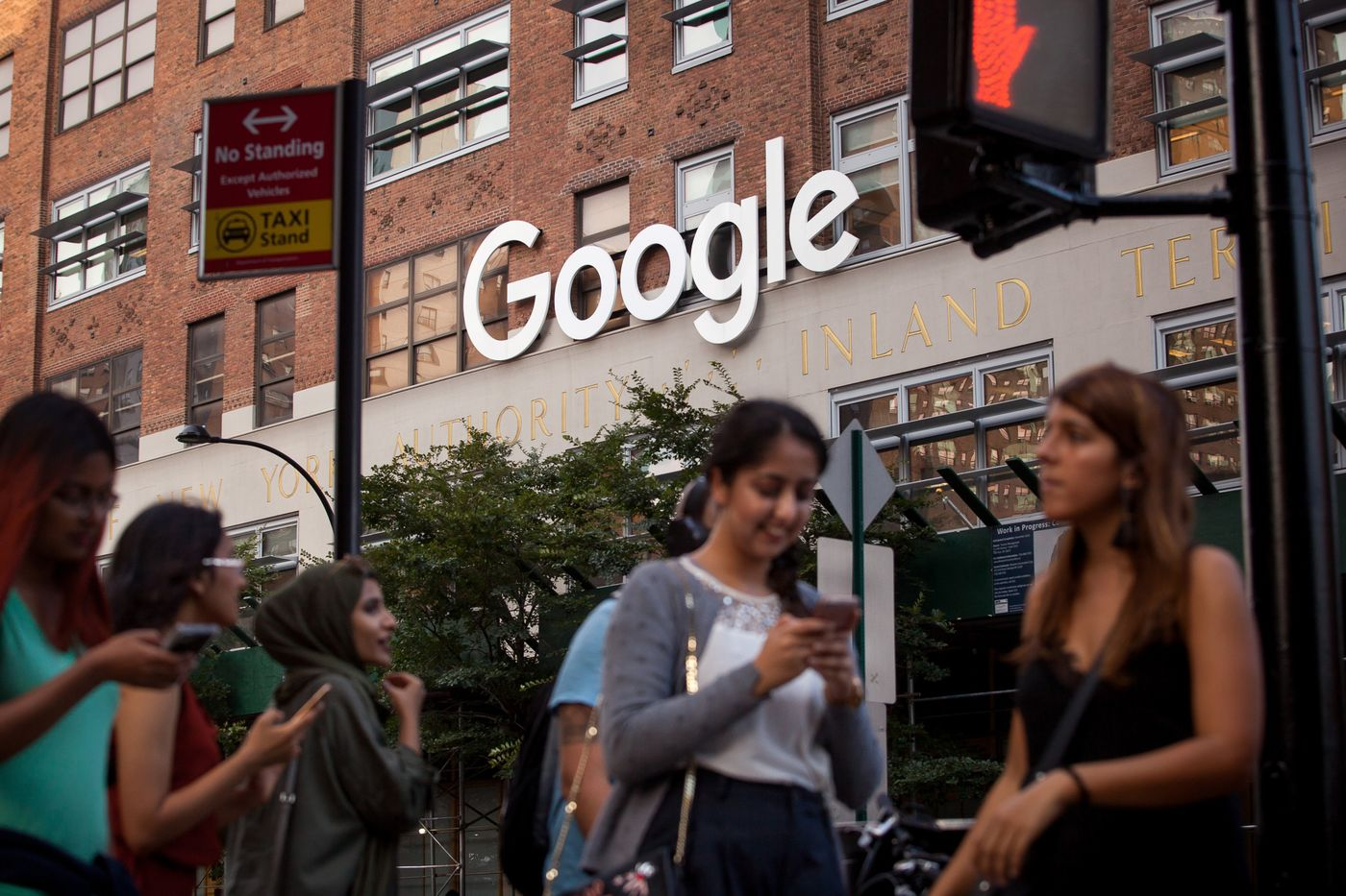 Pedestrians walk past the Google Inc. offices in New York, U.S.