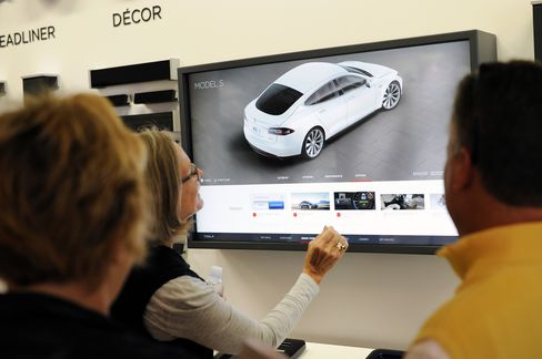Customers try out the Design Studio car customization kiosk at the Tesla Motors Inc. showroom in San Jose, CA, on Aug. 20, 2015.