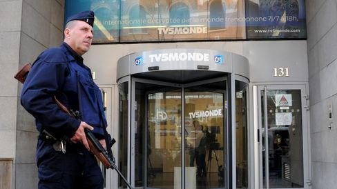 A policeman stands guard outside of the TV5Monde building after the cyber-attack in Paris, on April 9, 2015.