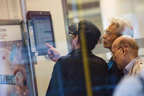 Customers look at a monitor displaying stock prices at a China Construction Bank Corp. branch.