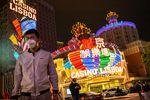People wearing protective masks walk in front of the Casino Lisboa, operated by SJM Holdings Ltd., at night in Macau, China, on Tuesday, March 3, 2020.