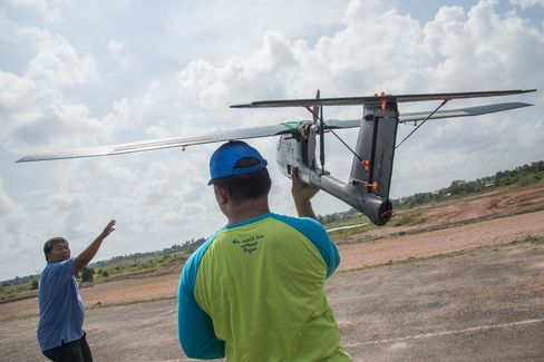 Members of the tax office prepare to launch a drone for a test flight at the Palembang military airbase complex. Photographer: Rony Zakaria/Bloomberg