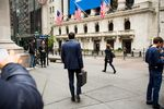 Pedestrians pass in front of the New York Stock Exchange (NYSE) in New York, U.S..