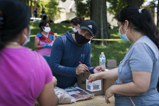 Mariano Espinoza distributes food to local residents during a pop-up grocery event at Powderhorn Park in Minneapolis on July 24, 2020.