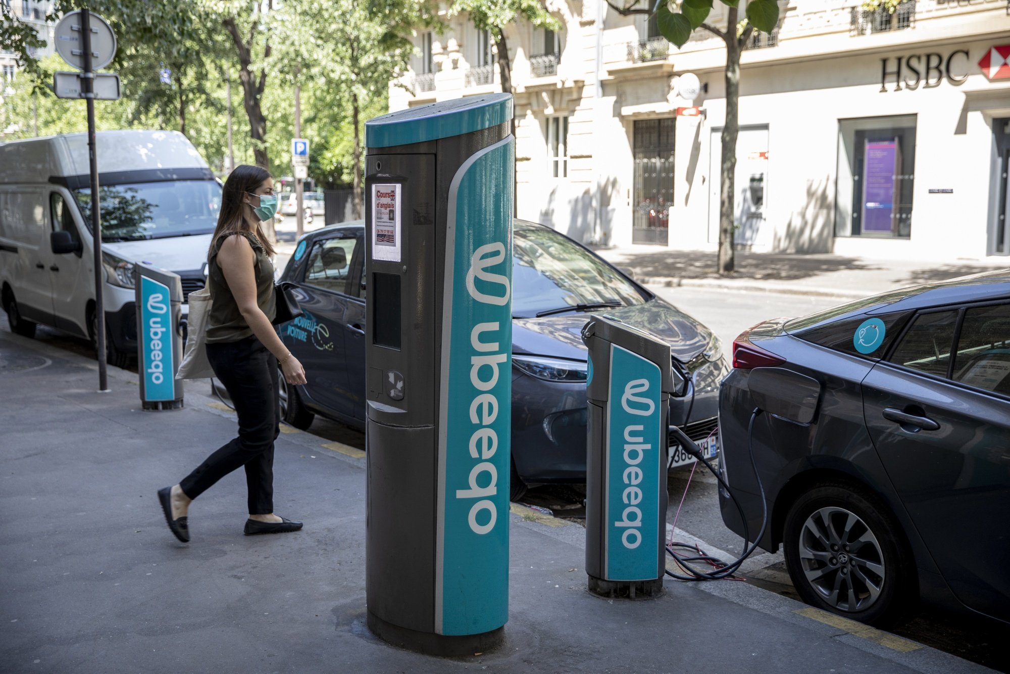 A pedestrianpasses electric automobiles charging at Ubeeqo SAS electric vehicle charge stations in Paris, France on May 27, 2020.